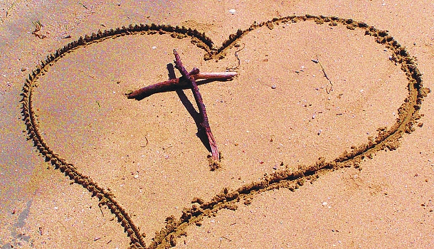 cross and heart in sand